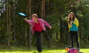 Two woman playing disc golf