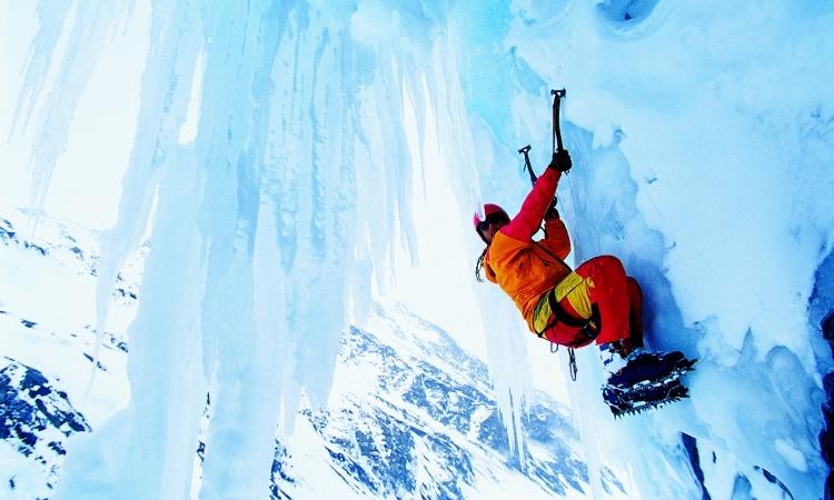 Man ice climbing up mountain