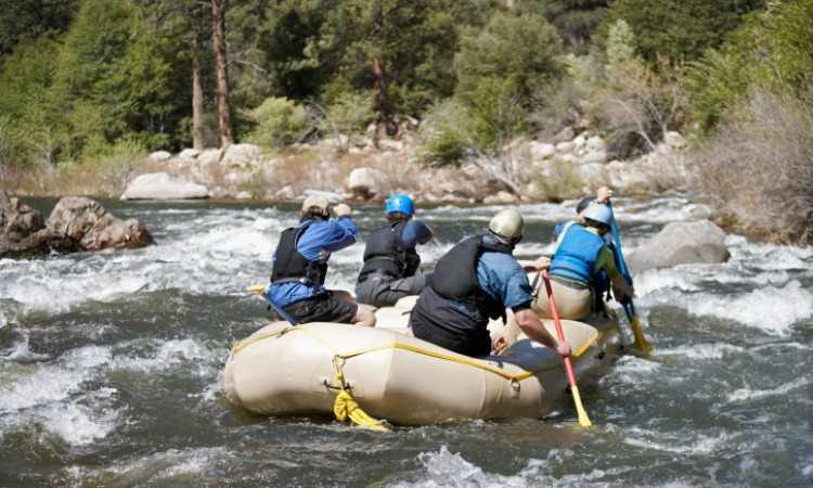 Four people on raft going down a river