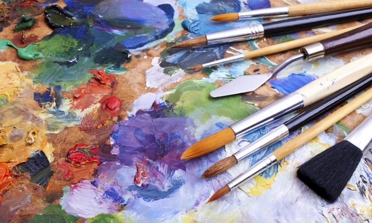 Closeup of paint on paper and paint brushes