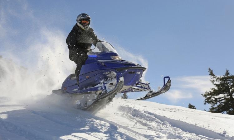Man on snowmobile going through snow